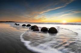 A line of Moeraki Boulders is silhouetted as the sun rises above the horizon, Coastal Otago, South Island, New Zealand - stock photo, canvas, fine art print